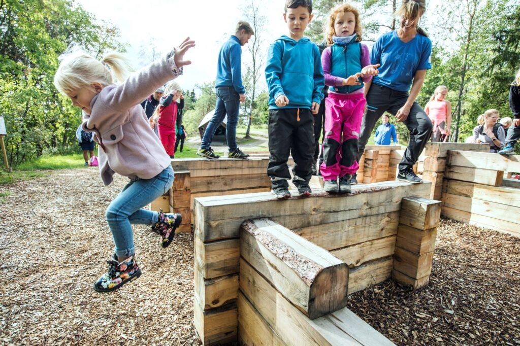 barn står och hoppar från trästockar