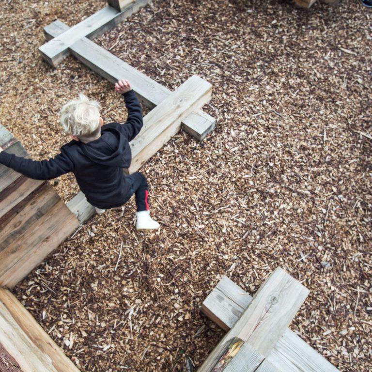 barn hoppar mellan stockar