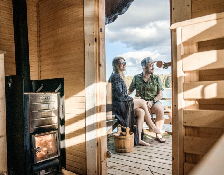 Bastu med eld. Två personer sitter på bänk