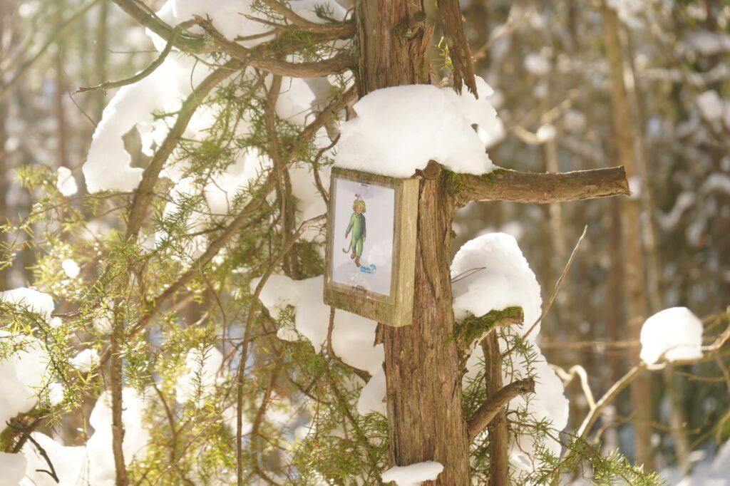 en skylt med ett tecknat troll sitter på ett träd