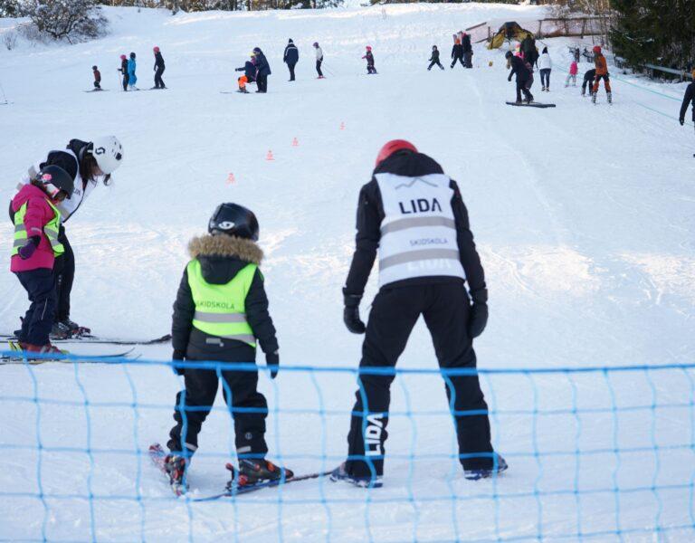 Barn och vuxna står i en skidbacke med snö