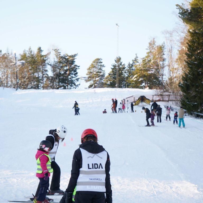 barn och vuxna står i en skidbacke