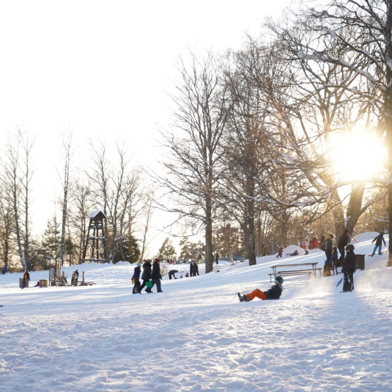 snö i en pulkabacke med barn som leker i solen