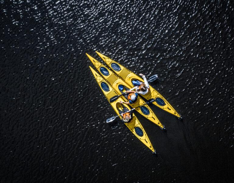 tre personer sitter i kajaker på vattnet