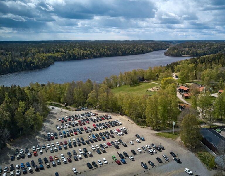stor parkering med många bilar vid en sjö och en skog