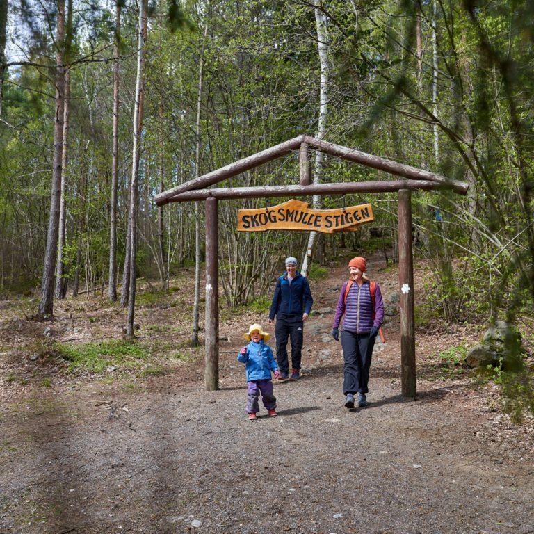 två vuxna med barn promenerar i naturen