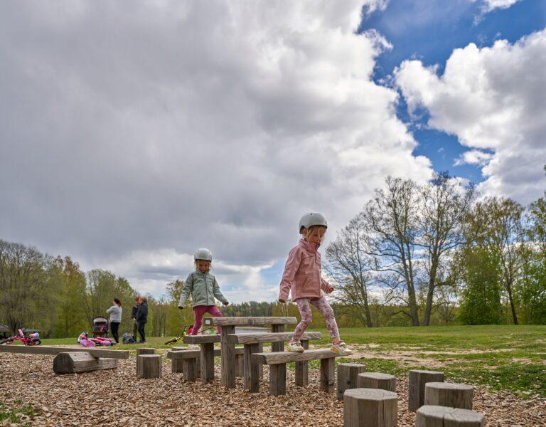 barn balanserar på stockar på en lekplats
