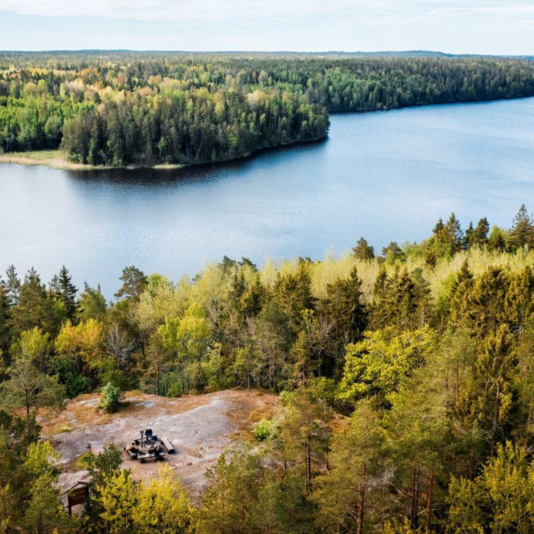 utsikt högt ovanifrån på en sjö, skog och personer som sitter vid en grillplats på ett berg