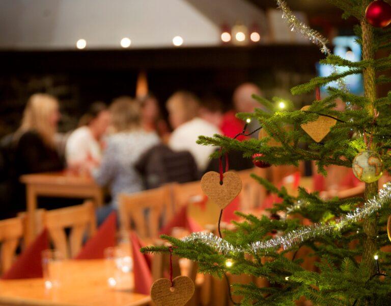 Julgran inne på restaurang. Människor sitter vid bord i bakgrunden