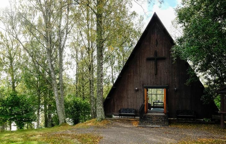 en träkyrka med ett kors som står i en björkskog