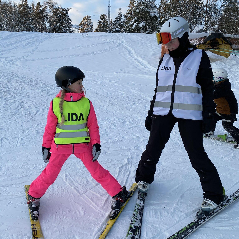ett barn och en skidlärare står bredvid varandra i skidbacke.