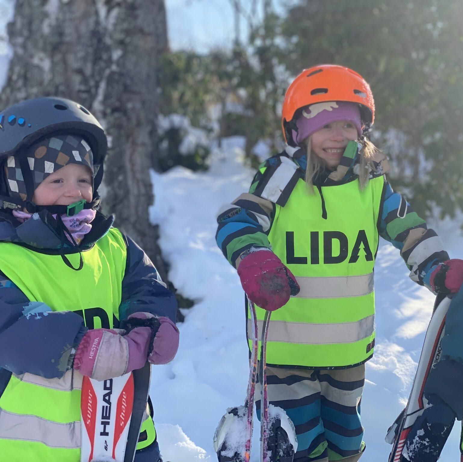 glada barn står i skidbacke. Håller skidor och har hjälmar på sig.