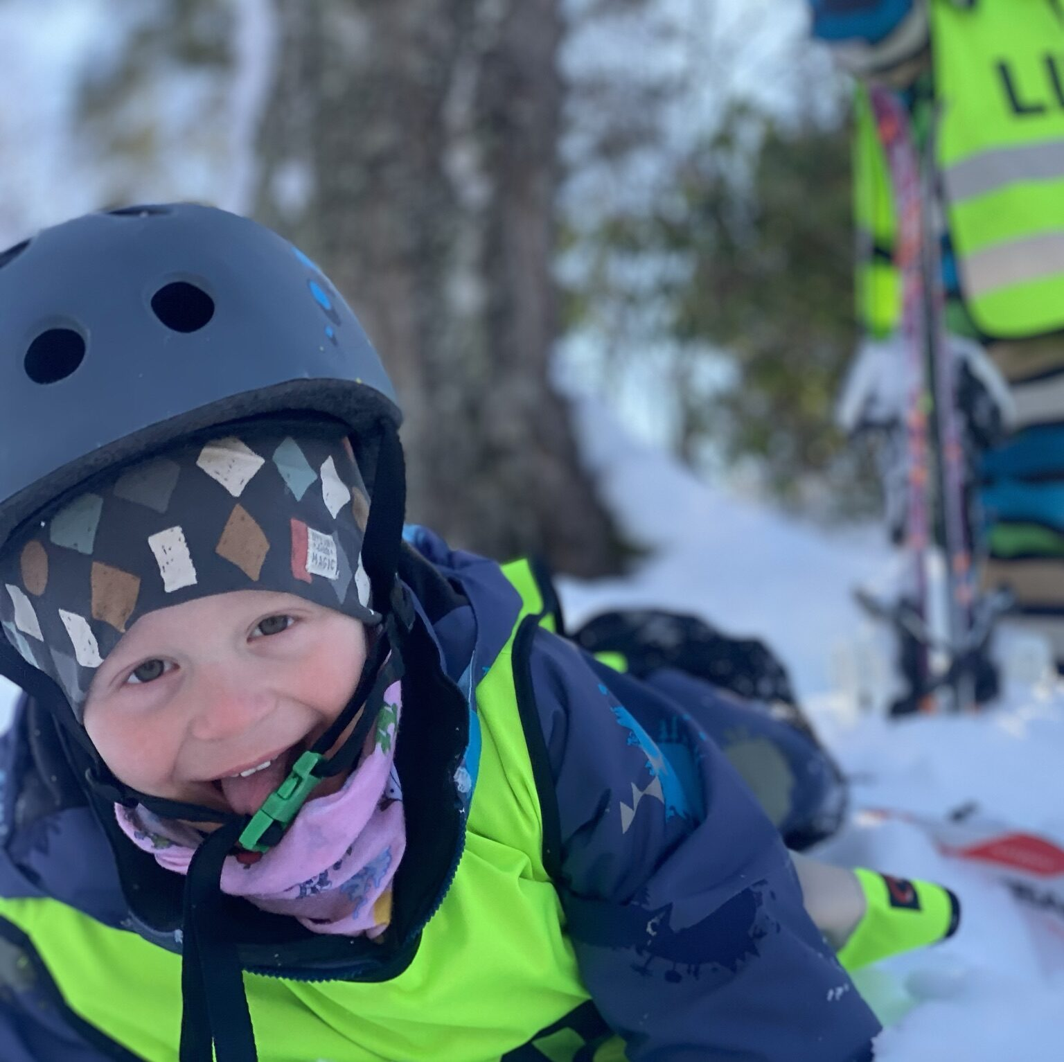 skrattande barn ligger i snön. Har hjälm, mössa och en väst på sig