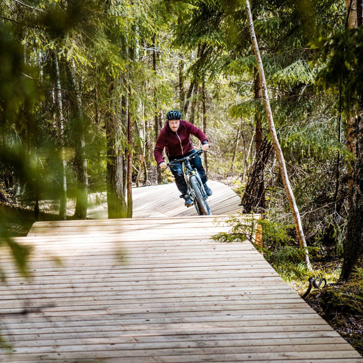mountainbikecyklist på träbro i skogen