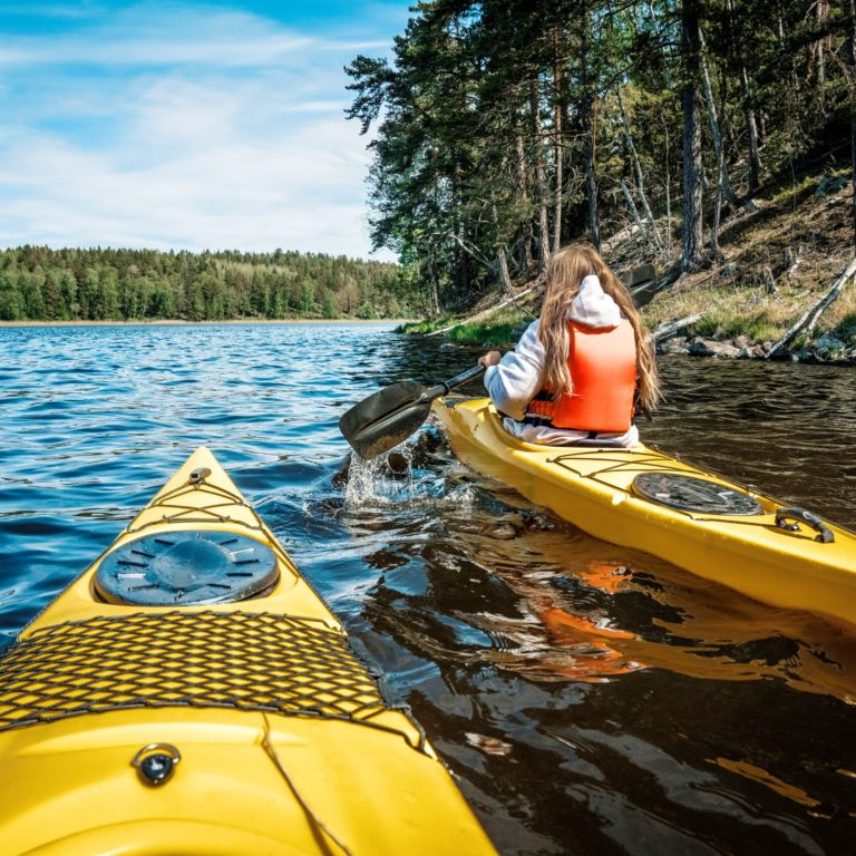 en person paddlar en gul kajakpå en sjö