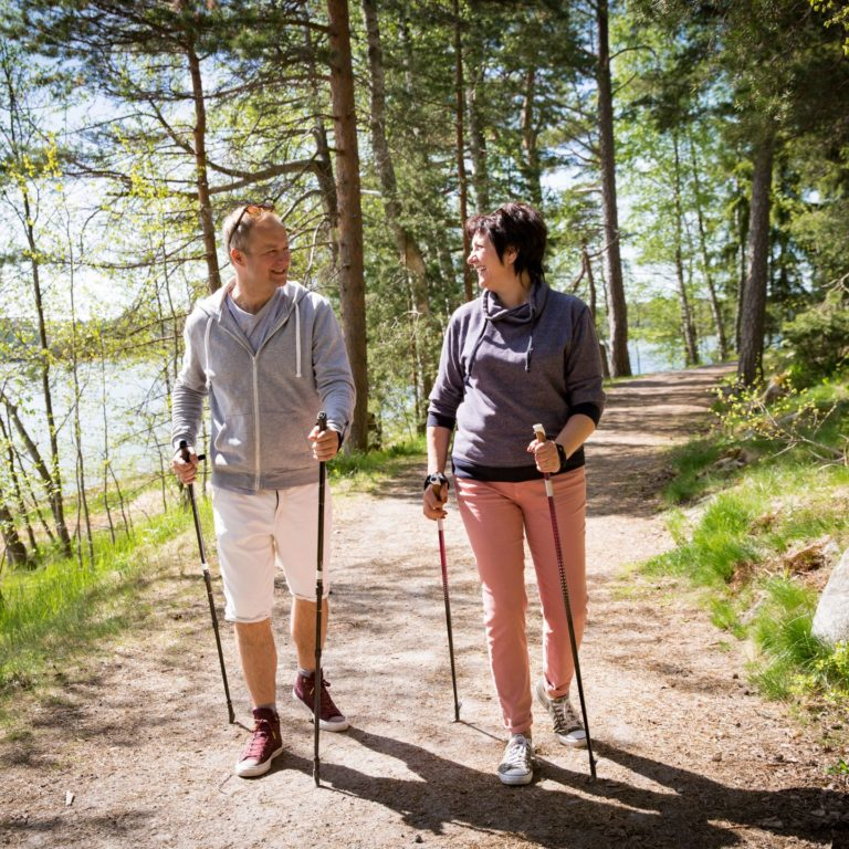 Två personer promenerar med gångstavar på skogsstig
