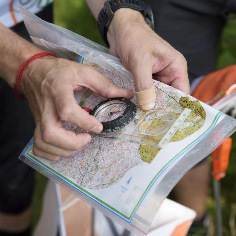 Person håller kompass och karta