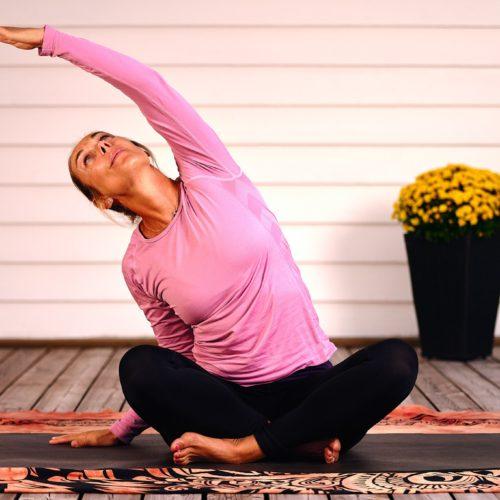 kvinna i rosa tröja sitter med benen i kors och armen utsträckt